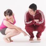 体重計に乗る男性と見ている女性