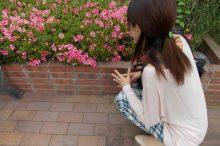 花壇のそばでヤンキー座りをしている女性