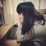 背中を丸めながらパソコンする女性